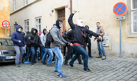 Útočník hází láhev do kolemjdoucího davu demonstrantů
