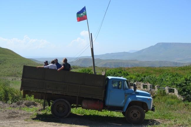 Moskvané odjíždějí z hradiště, v pozadí Karačajevsko-čerkesská vlajka
