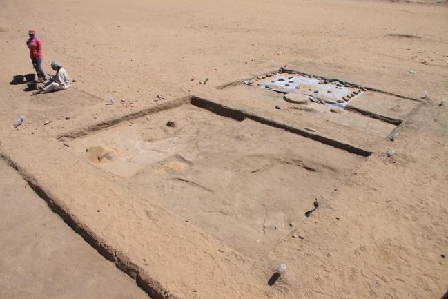 Sondy s částečně odkrytou pískovcovou dlažbou, sloupem a pečlivě zakrytými objevy.