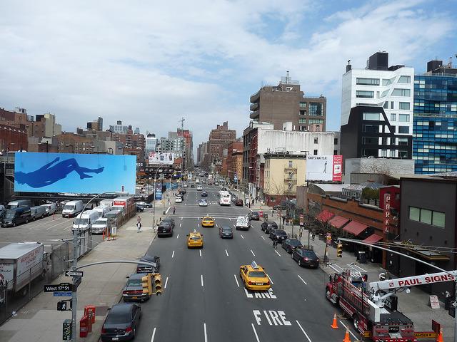"""Chelsea a 10. avenue viděná z High Line. Na billboardu dílo """"Blue Falling"""" Ryana McGinleyho"""
