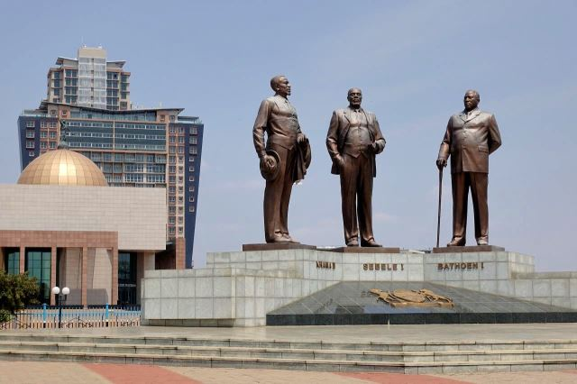 [Gaborone]Three Dikgosi Monument - pomník je věnován třem nejvýznačnějším Botswanům, v pozadí kopule justičního paláce