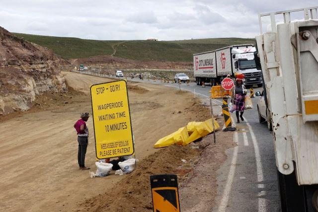 [Poblíž Mbashe Bridge]Začátek 17 km dlouhého úseku silničních prací - ženy nabízejí jídlo a pití čekajícím řidičům